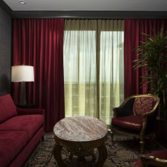 Red Couch And Curtains In Living Area